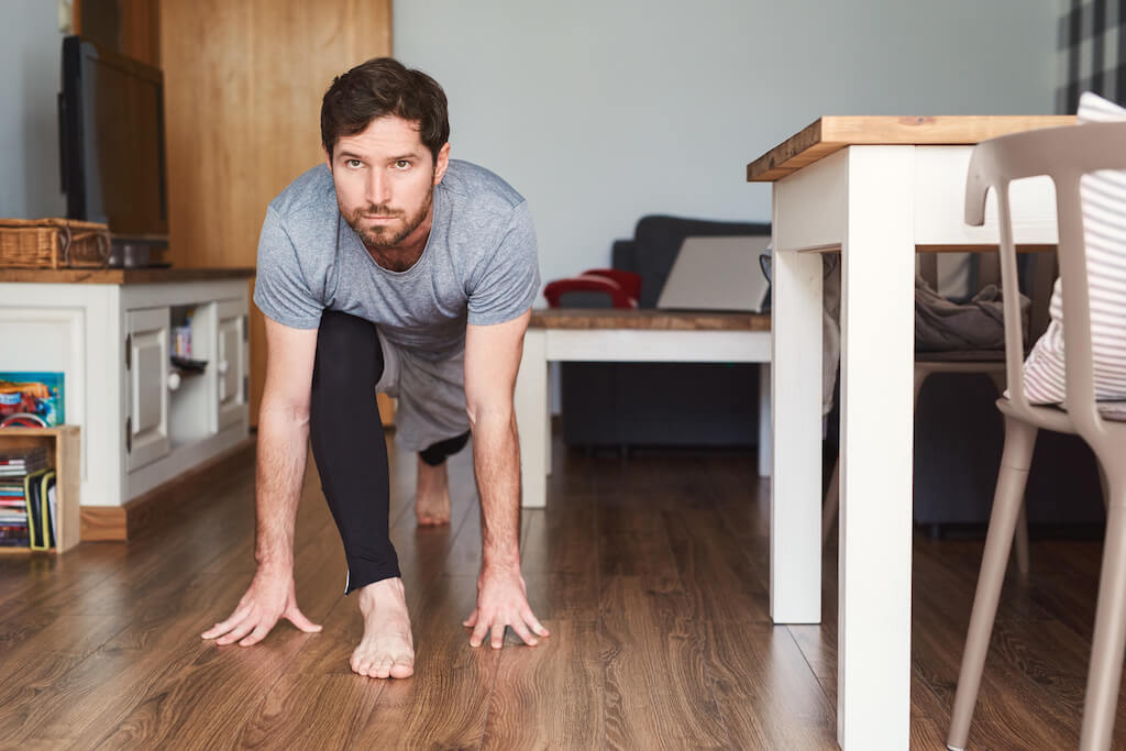 Fit young man in sportswear doing yoga at home